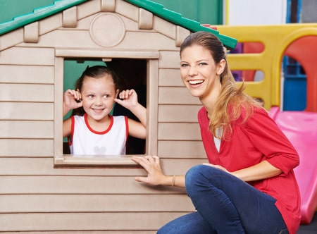 47628130 - happy educator playing with girl in playhouse in kindergarten